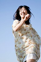 Young Woman Running Under Blue Sky