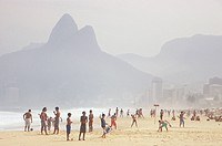 People play games and mingle near the shore with the Morro Dois Irm�£os in the background at Ipanema Beach, Rio de Janiero, Brazil.