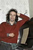 Roberto Benigni smiling. Italian actor and director Roberto Benigni smiling leaned on a piano. Italy, 1980