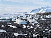 Iceberg on black vulcanic beach. North Atlantic beach of the ice lagoon Joekulsarlon at glacier Breithamerkurjoekull, Vatnajoekull NP. In background p...