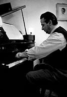 William Galassini playing piano. Italian conductor and composer William Galassini playing piano. January 1959