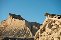 Cliffs eroded by rainfall juxtaposed to ruined traditional cattle shelter on clay-only area of the natural park of Bardenas Reales de Navarra, Navarre...