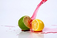 Red liquid pours down on a lemon and lime for a color contrast.