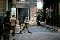 The police guard a road of Reggio Calabria. The police guarding a central road, where one can see a small fire still alight, following some troubles d...