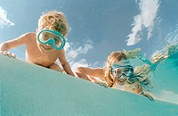 Boy and girl wearing diving goggles looking into water (Playa del Carmen, Cancun, Mexico)