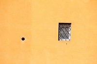 one small window with metal bars on property in rome italy