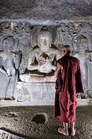 Buddhist monk in front of a sculture of Buddha in preaching attitude. on Cave 6th. Ajanta Cave. UNESCO World Heritage Site, near Jalgaon, Maharashtra,...