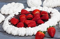 Meringues and meringue baked pastry case with chocolate icing garnished with strawberries on grey wood