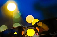 sunglasses with city lights background.