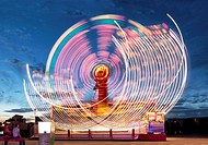 Lighted ferris wheel in amusement park at night. Illuminated attraction in the move.