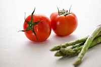 two tomatoes and several asparagus on a table