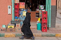 Woman wearing moroccan niqab walking by a shop on the streets of Rissani, Ziz Valley, Morocco.