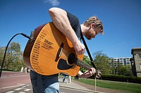 Busking musician with amplified acoustic guitar list of places visited.