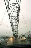 Driving on the Bridge of Americas over Panama Canal during tropical rain.