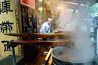 Muslim soba noodle soup kitchen with a Muslim cook and large steaming pots on an iron stove at Xi´an LianHu Historical and Cultural Blocks.
