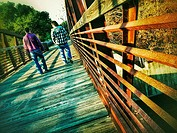 Two men walking casually into the distance across an iron bridge expressing a feeling of comfortable friendship