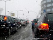 View through the windshield, snow falling, cars waiting in front of the traffic light