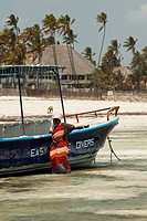Local woman with colorful traditional clothes standing close to a boat in the sea, Paje, Zanzibar Island, Zanzibar Archipelago,Tanzania, East Africa.