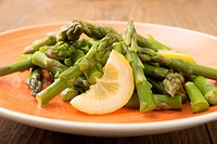 Green asparagus with slice of lemon on plate