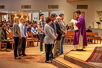 Catechumens, or people wishing to become Catholics, meet with their sponsors before a robed Vietnamese American priest for scrutiny at a Catholic chur...