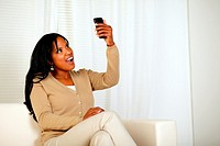 Portrait of a surprised woman holding her cellphone up while is reading a message at home indoor.