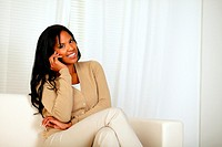 Portrait of a black woman smiling at you while sitting on sofa and speaking on mobile phone at home indoor.