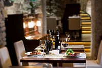 a view on the interior of the restaurant, a table set for two with wine, a dish of sirloin steak with red onions, tomatoes and rocket leaves and a dis...