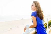 Woman Leaning on Railing of Beach Promenade