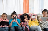 Children using technology on sofa