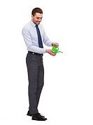 business, ecology and office concept - handsome buisnessman with green watering can