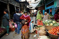 A woman looking through her purse at the main Darjeeling Market where you can buy fresh produce, spices and goods.