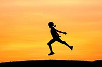 An active girl leaps in the air during a bright orange sunset.