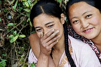 Portrait of two young Tibetan female Labor workers embracing and laughing with each other.