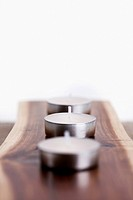 three candles on top of a wooden plate