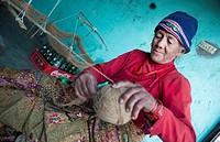 Nepal. Nepali weaving woman, posing and weaving threads for carpets. Nayapati, Eastern Kathmandu. 43.
