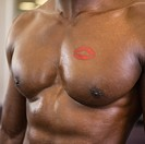 Shirtless muscular man with lipstick mark on chest