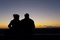 Couple watching sunset, Es Codolar Boulder beach, Eivissa, Ibiza, Balearic Islands, Spain, Mediterranean, Europe.