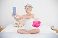 Funny natural brown haired woman in hair curlers taking picture of herself with a tablet
