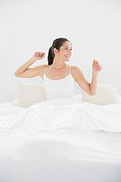 Smiling woman stretching her arms in bed
