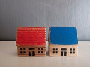 Two miniature houses on a grey background.