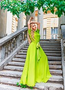 Beautiful woman in long green dress outdoors