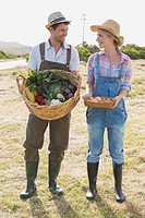 Full length of couple with vegetables in field