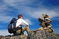 Hiker and rock cairn on trail, Hudson Bay Mountain, Smithers, British Columbia.