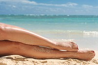 Close up of Hispanic woman's sandy legs on tropical beach