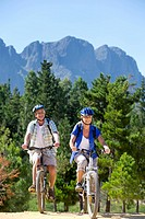 Older couple riding mountain bikes in forest
