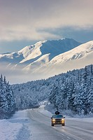 Clouds clearing over Seward Highway from the Kenai Mountains above Turnagain Pass after a winter snow storm, fresh snow in the trees, early morning su...