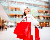 happiness, winter holidays, christmas and people concept - smiling young woman in white hat and mittens with red shopping bags over shopping center ba...