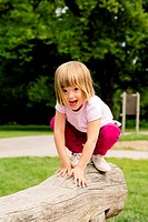 Little girl on playground crouching on log