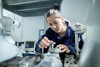 Female engineer turning valves on factory industrial piping