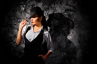Woman with cigar on grey wall background